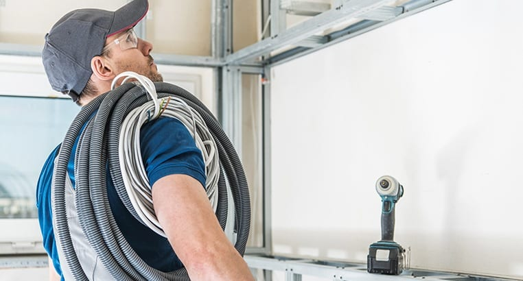 Electrician with cables around their shoulder