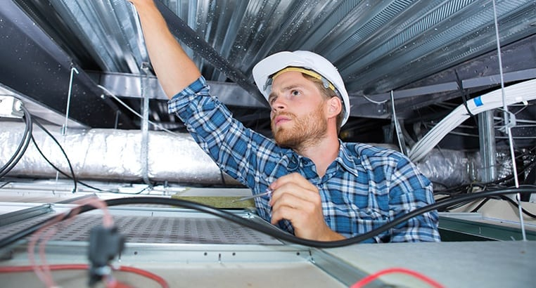 Electrician inspecting area above ceiling