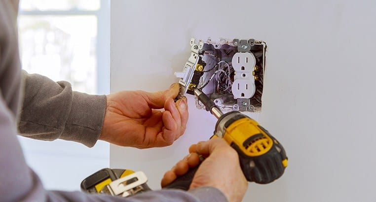 Electrician working on electrical outlet
