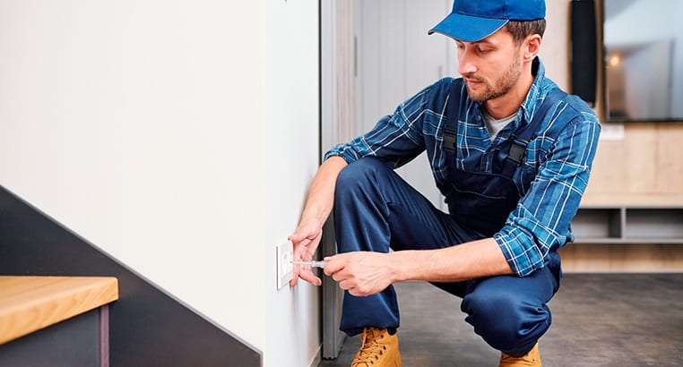 Electrician screwing an electrical outlet plate to a wall