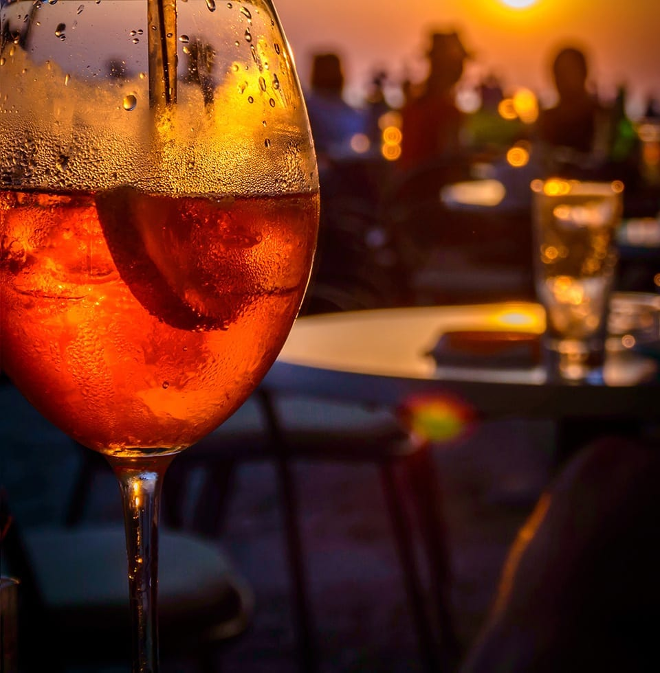 Glass of a BarBox cocktail in the sunset